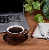 Cup Of Coffee With Steam On A Wooden Desktop With A Notebook And Laptop Computer poster