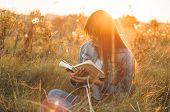 Beautiful Girl In Autumn Field Reading A Book. The Girl Sitting On A Grass, Reading A Book. Rest And poster