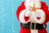 Santa Holding A Starfish On A Shiny Light Blue Background poster
