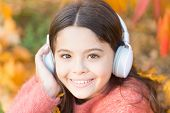Give In To The Groove. Happy Child Wear Headphones. Little Music Fan On Autumn Day. Happy Little Gir poster