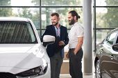 Manager Holding Folder And Showing To Customer Of Car Center White Automobile. Men Standing Near Aut poster