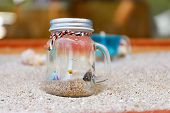 Bottle Of Water And Sand On The Sand Beach poster