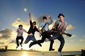 stock photo of attitude boy  - Band of young male musicians jumping with instruments against sunset sky background - JPG