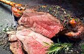Traditional barbecue leg of lamb with spice and herb as top view on a metal sheet  poster