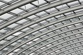 stock photo of purlin  - Section of the curved reinforced steel roof joists in a conservatory with glass panes in between - JPG