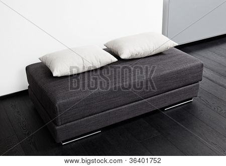 Dark gray padded stool with white pillow, detail of modern sitting room interior in black and white