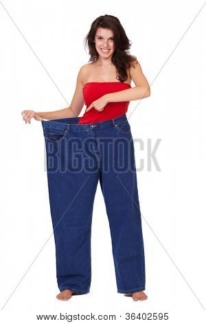 Young happy attractive female in huge old pair of jeans, diet concept, isolated on white