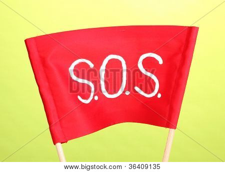 SOS signal written on red cloth on green background