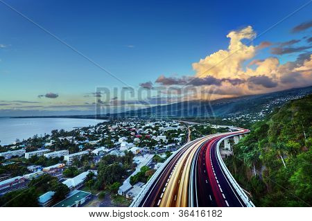 Scenic view Bay of Saint Paul with colorful slow motion effect traffic lights on highway in foreground, Reunion Island.