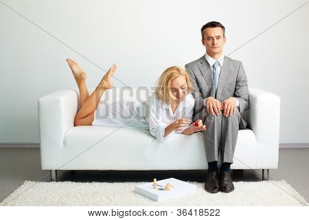 Tensed entrepreneur trying not to pay attention to a sexy female doing her nail nearby