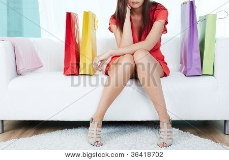 Close-up of stressed shopaholic sitting on sofa surrounded by paperbags
