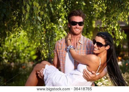 Romantic young couple smiling in the garden, man holding girl in arms.