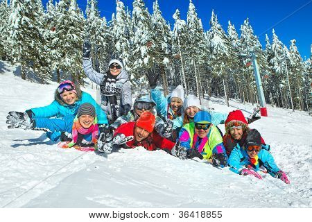 Group of teenagers laid on the snow in wintertime