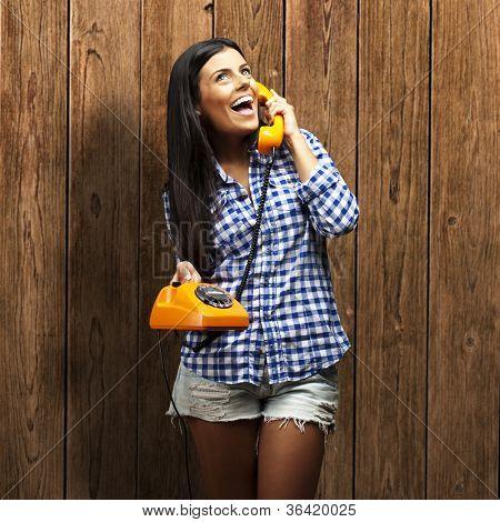 retrato de jovem mulher falando no telefone vintage contra uma parede de madeira