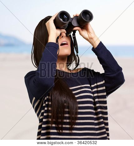 portrait of young woman looking through binoculars against a beach