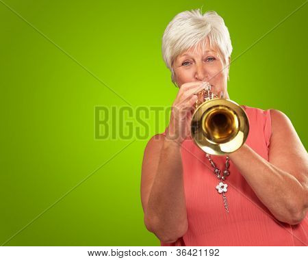 Mature Woman Blowing Her Trumpet Isolated On Green Background