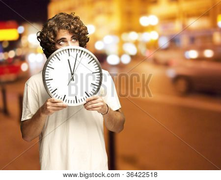 young man hiding behind a clock against a city night background