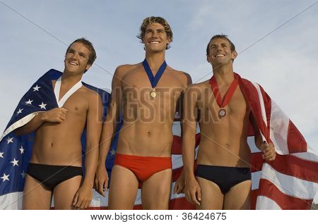 Happy swimming champions holding an American flag