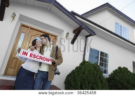 Portrait of a happy couple kissing outside new house