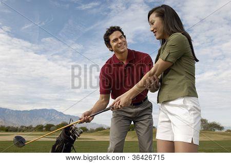 Feliz homem maduro, ensinando a mulher a jogar golfe