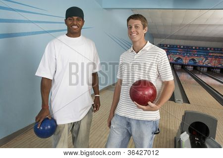 Portrait of multiethnic male friends at bowling alley holding ball