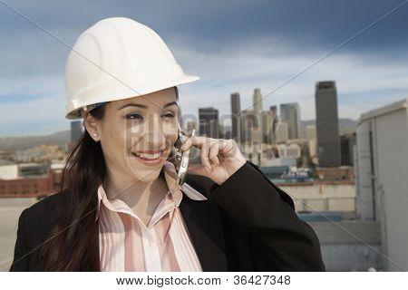 Happy female architect wearing hard hat talking on phone