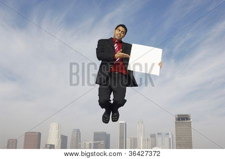 Mixed race businessman in midair showing a blank placard