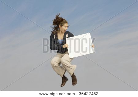 Full length of a mixed race businesswoman in midair holding a blank placard