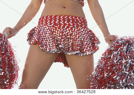 Midsection of a female cheerleader holding pompoms