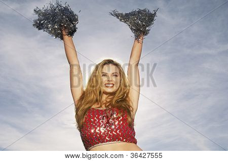 Low angle view of a Caucasian cheerleader cheering with pompoms raised against sky