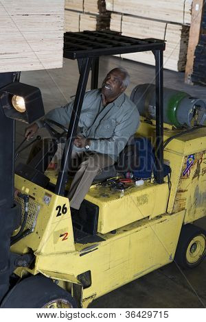 African American senior man driving forklift