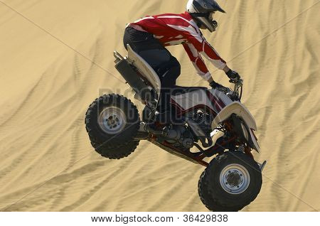 Quad bike rider jumping over sand in desert