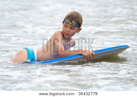 Young child with a bodyboard on the beach