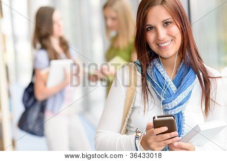 Female student listen mp3 player in high school hall