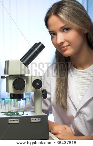 beauty researcher looking through microscope in laboratory