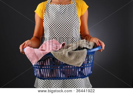 Closeup of a homemaker in an apron holding a basket full of laundry. Horizontal format over a light to dark background. Woman is unrecognizable. Shallow depth of field.