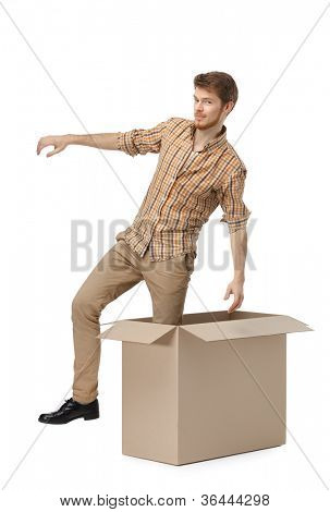 Young man gets out of the cardboard box, isolated, white background