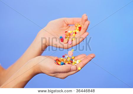 Pills, tablets and drugs pouring in doctor's hands on blue background