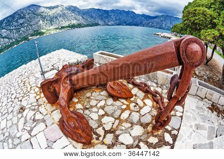 Old anchor on the waterfront on mountains background. Fish-eye view. Montenegro