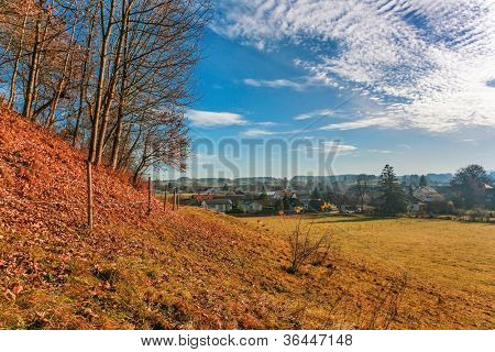 Autumnal field with village on background uner blue sky