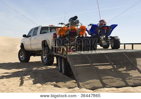 Quad bikes on trailer in desert