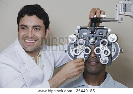 Hispanic Male optometrist with phoropter while examining patient
