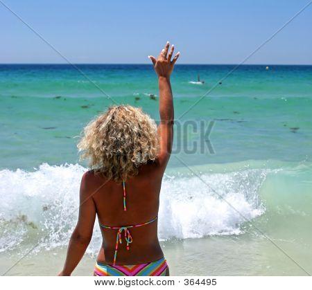 Woman In Bikini On White Beach Waving To Her Husband