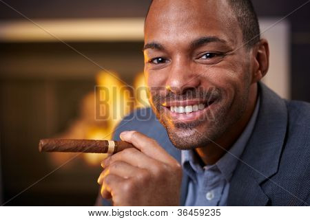 Happy ethnic man smoking cigar by fireplace, smiling, looking at camera.