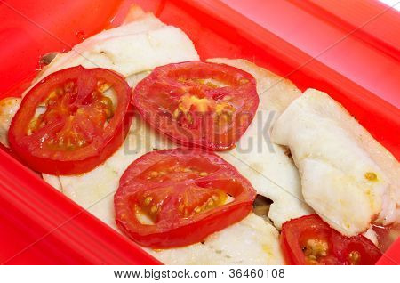 some slices of hake cooked en papillote with slices of tomato and other vegetables