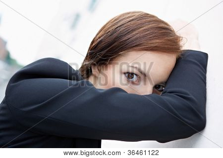 Shy business woman hiding behind her arm