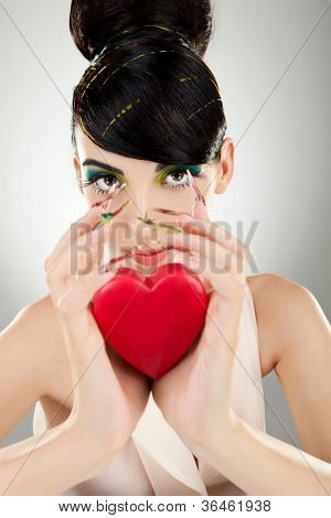 Attractive young woman model with excentric make-up and manicure holding a heart