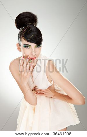 Picture of a ravishing young woman smiling while holding her hand on her belly. on gray background