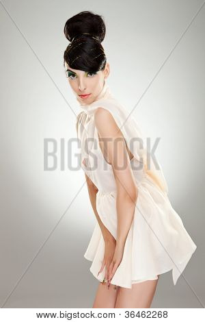 lovely young woman in fashion white dress looking at the camera and holding hands near crotch zone. on gray background