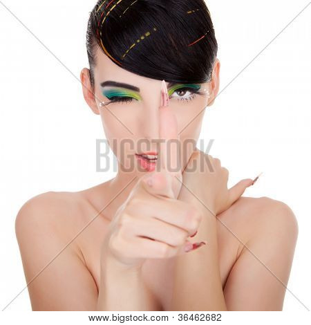 young woman makes gun with her hands while she winks. Young model shooting you and winking. On white background